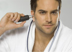Mid adult man using ear hair trimmer